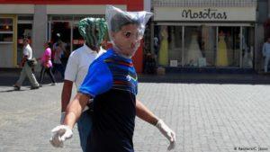 dos hombres cubren sus rostros con bolsas de plástico en Carcacas, para protegerse del coronavirus.